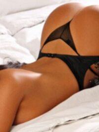 Toronto escort Megan half naked in a bed