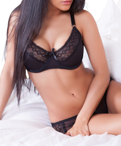 Busty brunette sitting on a bed wearing black bra and black panties