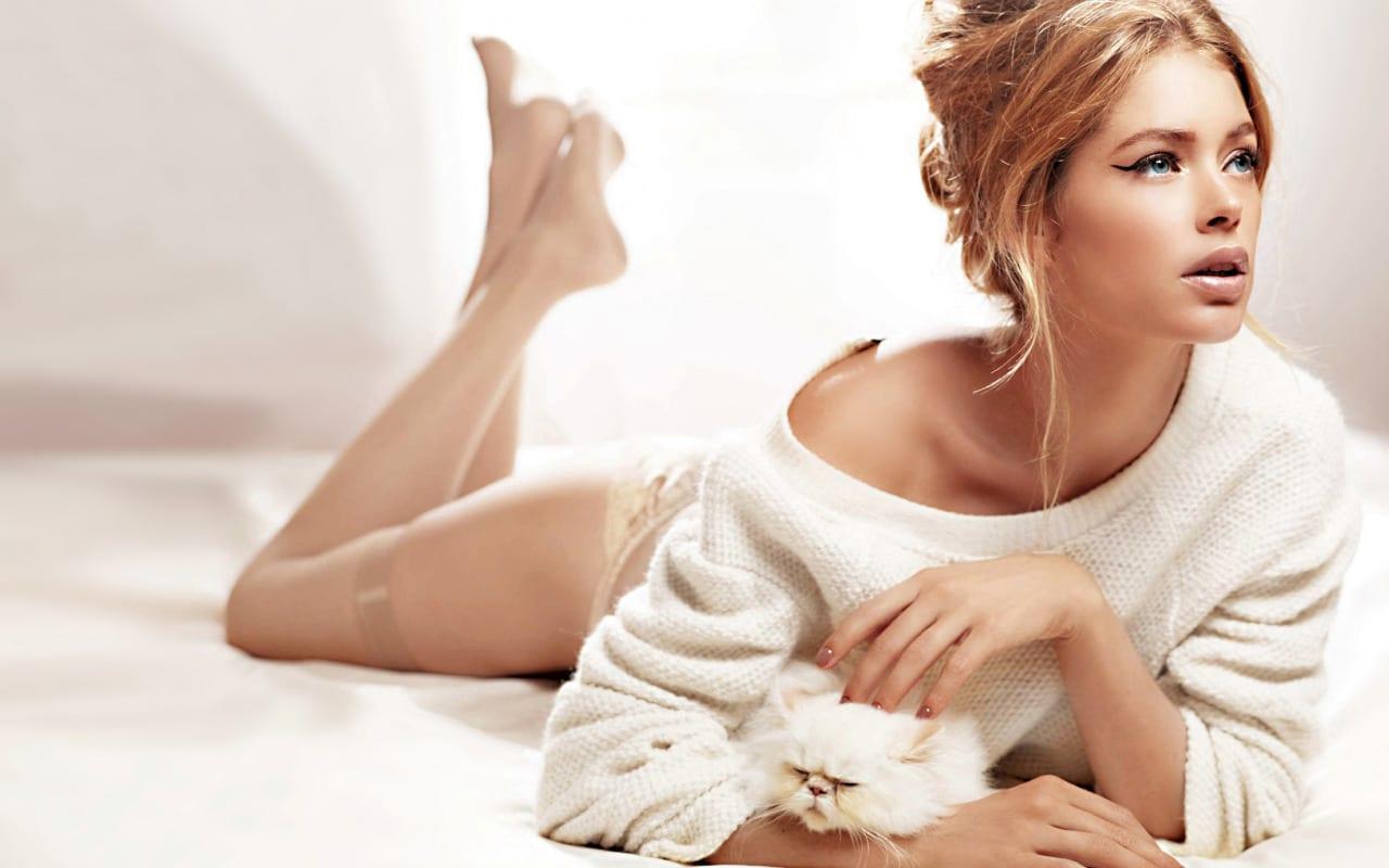 Beautiful Blonde escort seating in bed