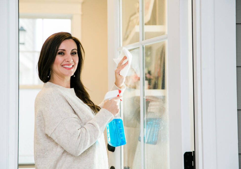 woman cleaning the windows to the outside of a front door