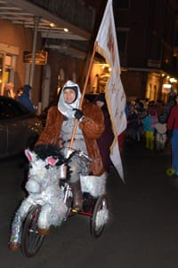 Joan on a horse tricycle carrying the lifesize replica of Joan's banner