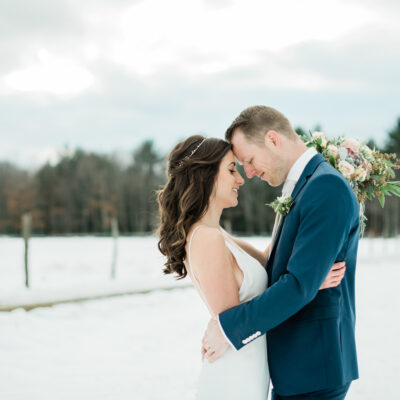 couple standing in the snow embracing on their wedding day