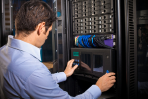 An IT technician programming computer equipment in a server room