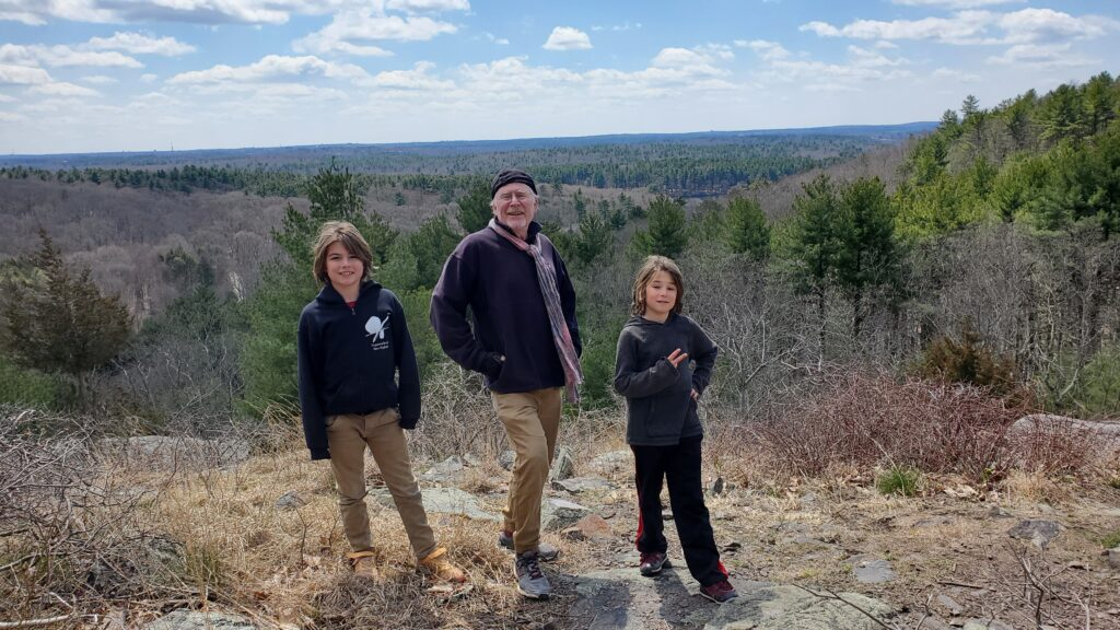 Daddio and the twins at Blue Hills Reservation, with a sweeping vista in the background