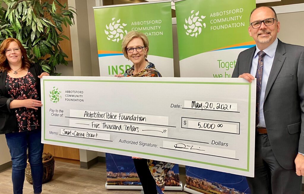 Kevin Boonstra and Sandy Blue accept a cheque from Densie Thandi, Abbotsford Community Foundation in support of YMPC.