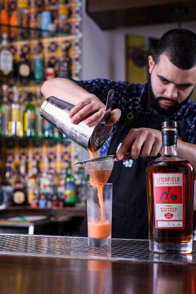 Mixology Spirit guest Sammi Reyes straining cocktail