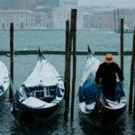 Gondolieri reading his gondola with snow