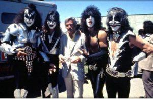 The members of Kiss, in full makeup, flank Stan Lee.