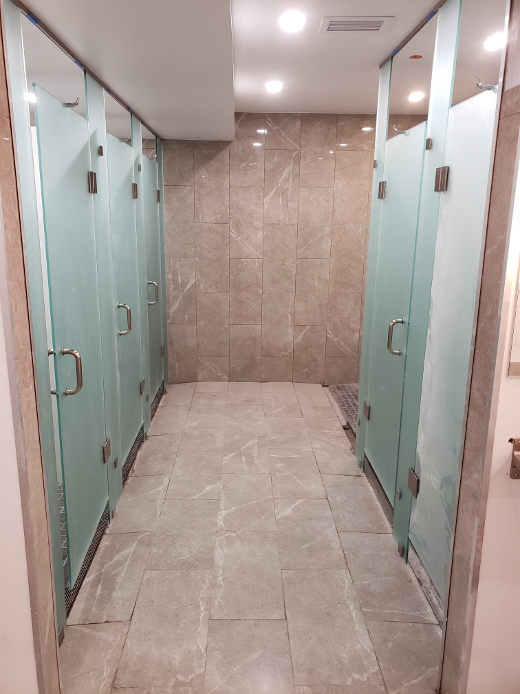 Acid-etched glass shower enclosure in gym