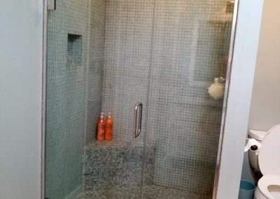 jamb mounted shower on glass tile