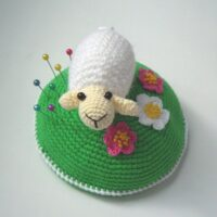 Little white sheep on blooming green lawn Pin Cushion by Ksenia Design
