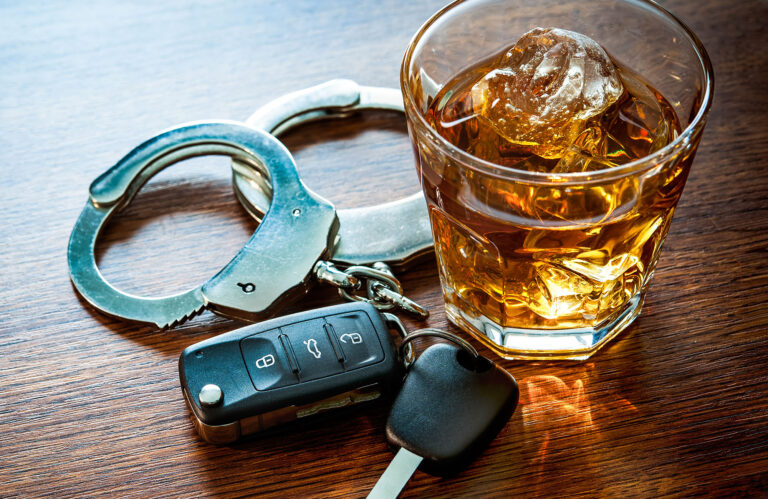A photo of car keys, an alcoholic drink, and handcuffs. - April is DUI Awareness Month. Don't Drink and Drive!