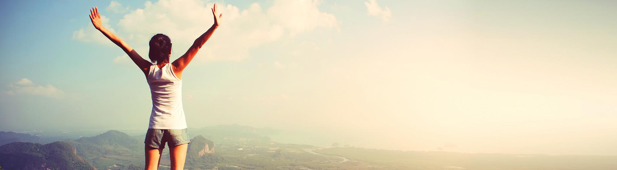 woman hiker enjoy the view on mountain peak cliff