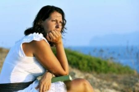 Woman looking into the distance with book on lap and ocean in background