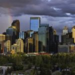 Calgary downtown skyline with dark clouds and small rainbow during sunset