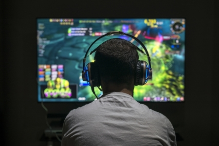 Teenager in front of large screen playing video game with headphones on