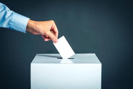 Person placing vote card in ballot box