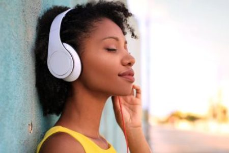 Woman happily listening to music on headphones