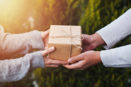 One person giving a gift to another person