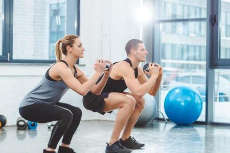 Man and woman exercising hard at gym