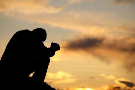 Man praying by sunset