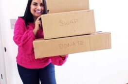 a woman in a pink sweater holding a stack of boxes that say salvage, donate, swap, sell