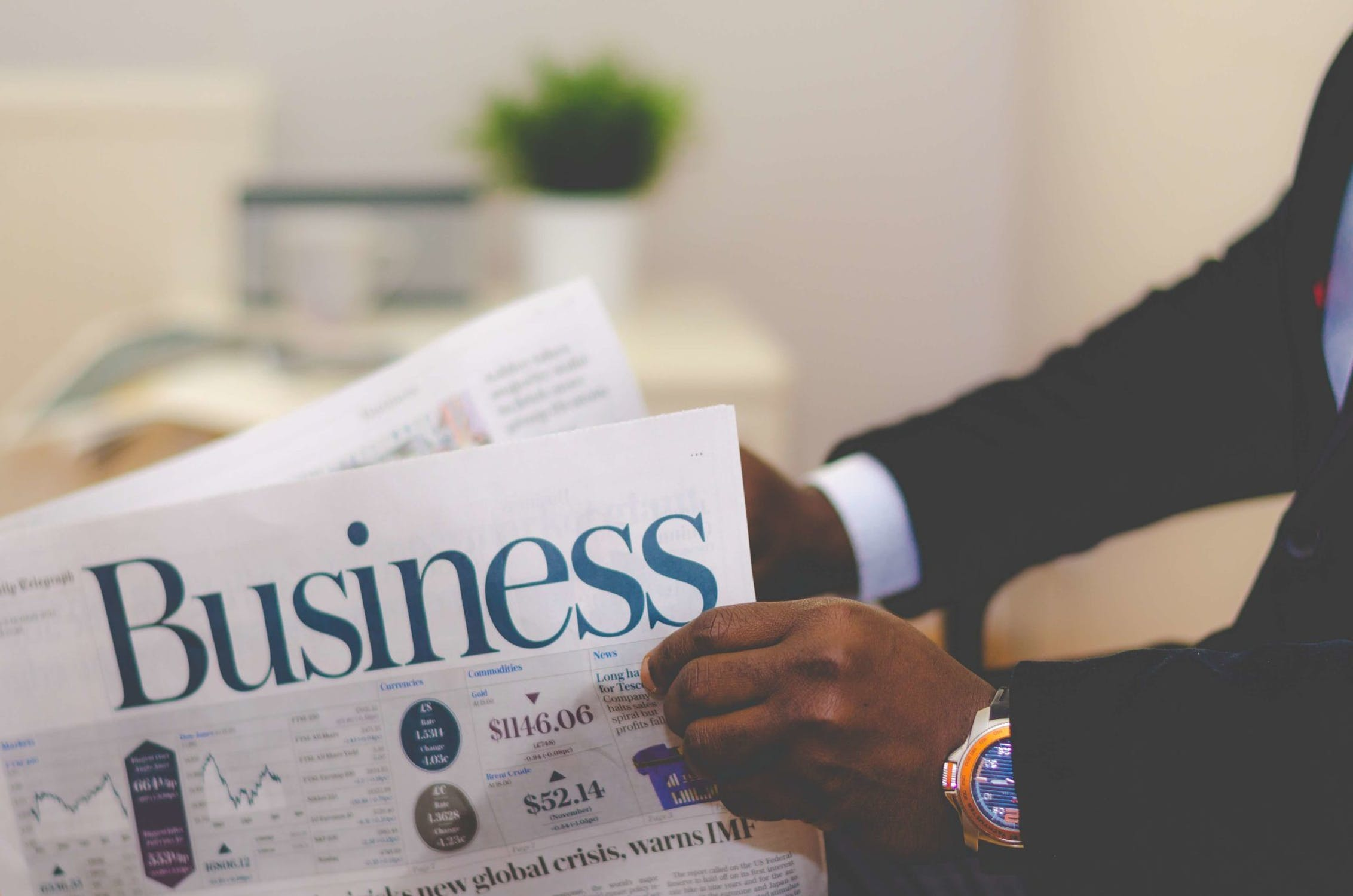 Hands of a man in a suit with the business section of a newspaper.