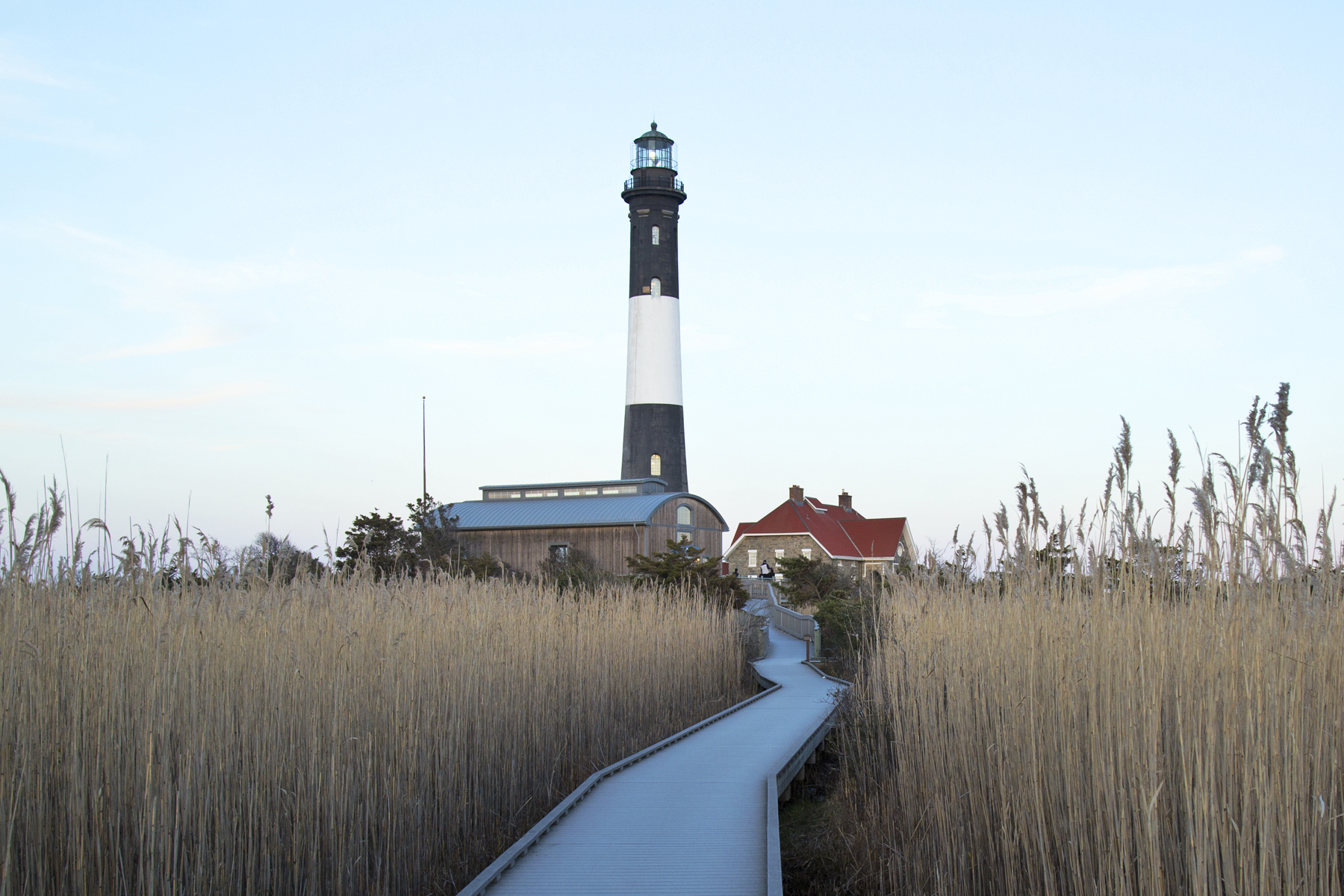 A lighthouse on Long Island, with a walkway leading to it.