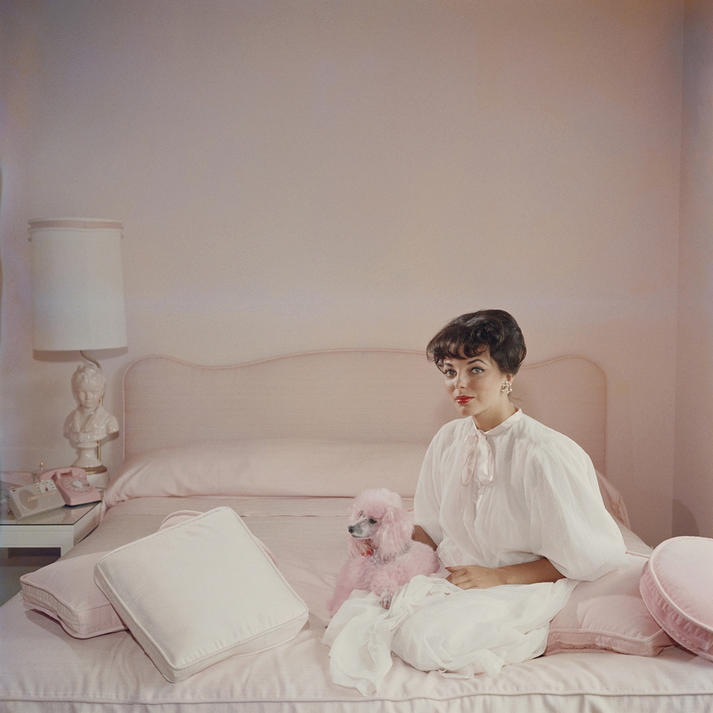 Who wouldn't want this framed Slim Aarons photograph of Joan Collins in a pink and white bedroom with a pink poodle, circa 1955, on their wall? $1,450 @jonathanadler.com