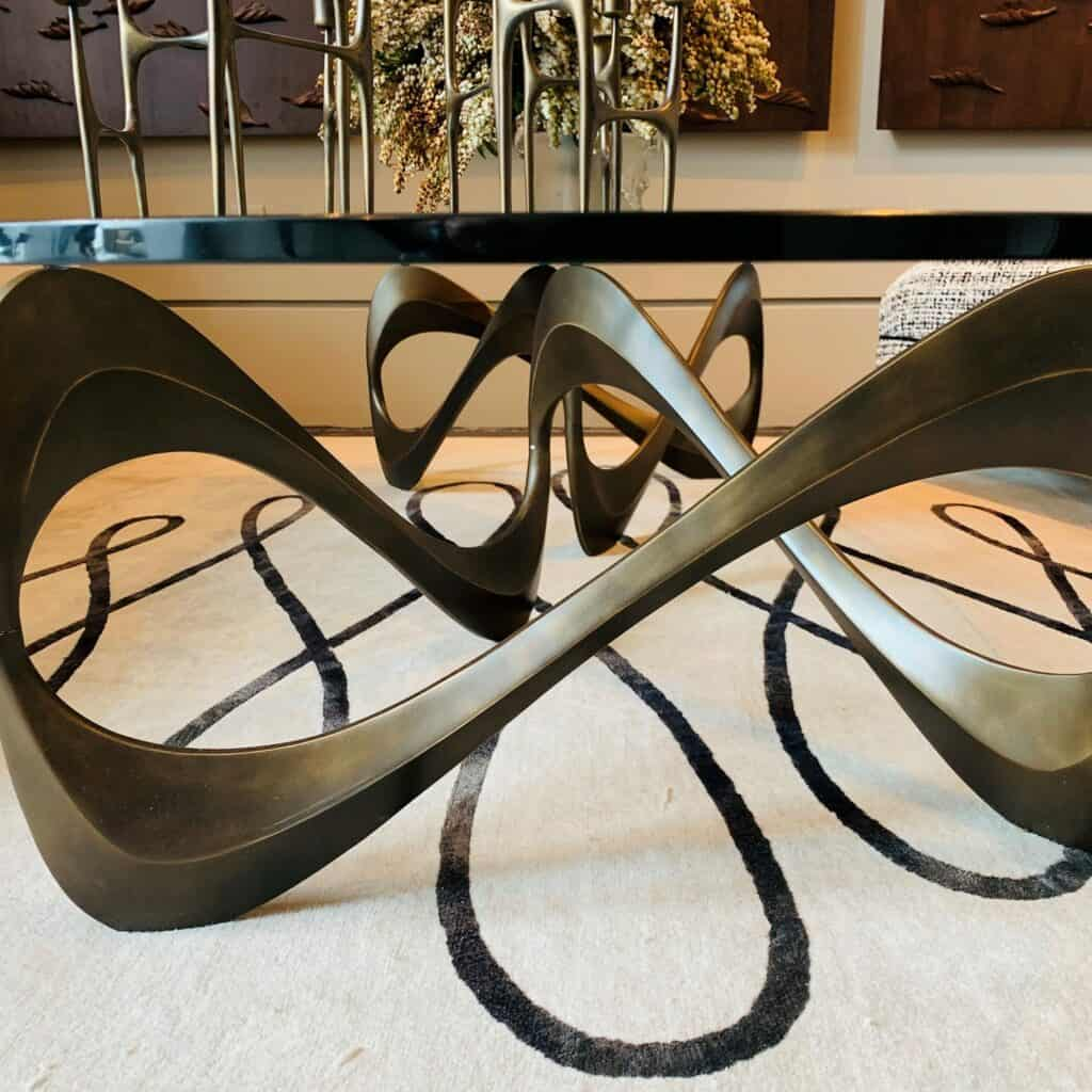 Curved metal base cocktail table. Endless movement.