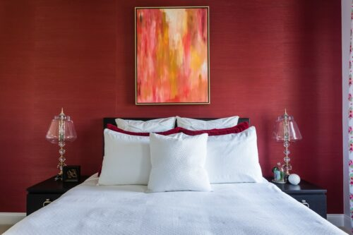 Abstract art in warm tones on a red grasscloth wallpapered wall. Guest bedroom design.