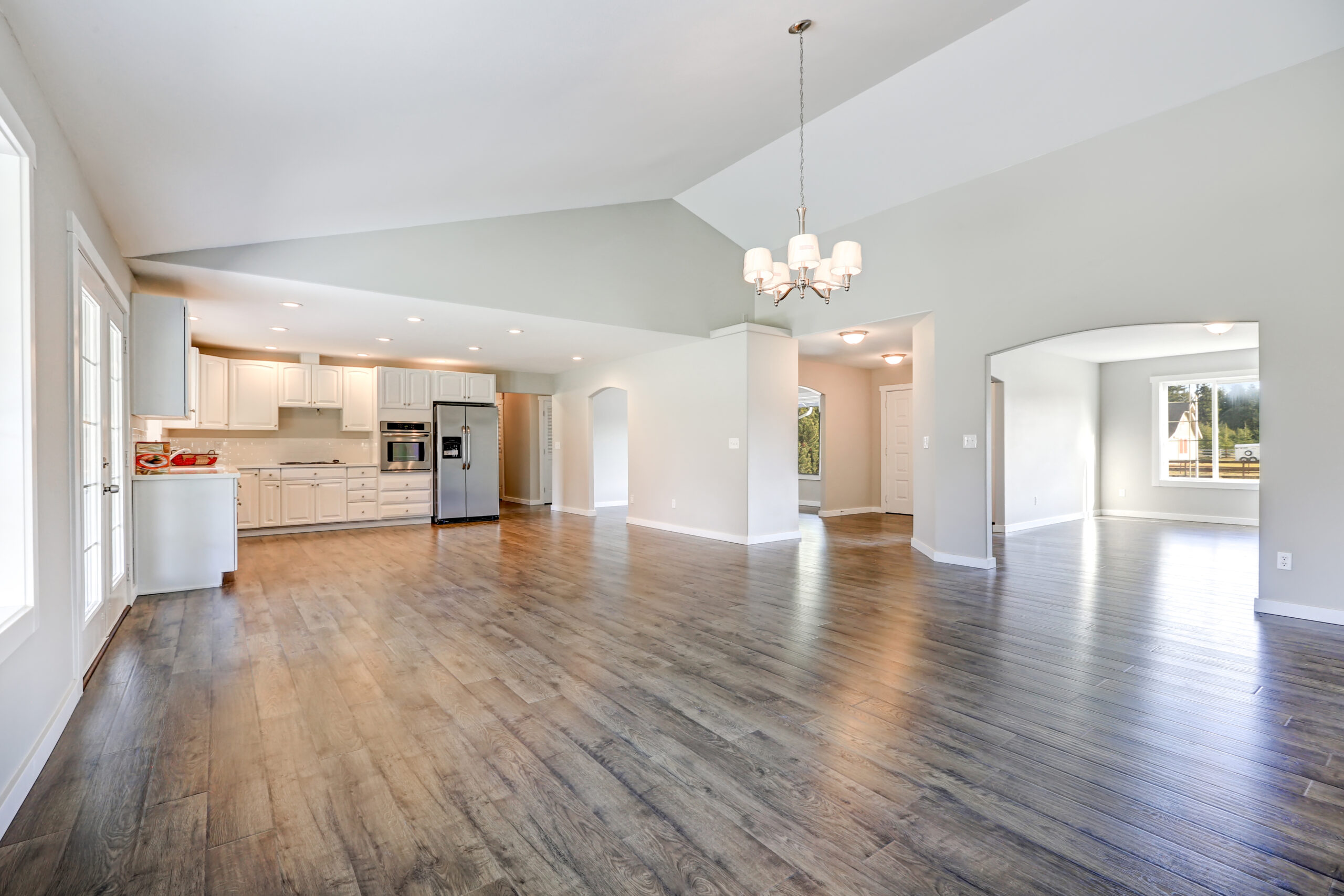 Spacious rambler home interior with vaulted ceiling over glossy laminate floor. Empty light filled dining or living space adjacent to new white kitchen room features pale grey walls. Northwest, USA