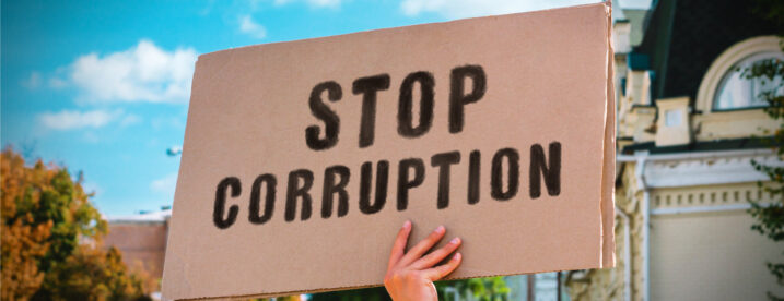 Man holds cardboad sign reading 'Stop Corruption.'
