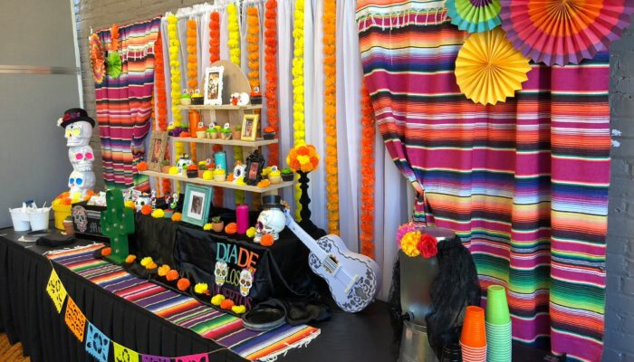 Photo of a party room and setup at Tiny Town — a colorfully decorated buffet table with a Dia de los Muertos theme