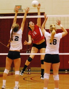 Maria Mayer hits between two Fullerton blockers on Tuesday night.