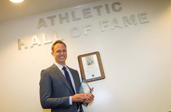 Chris Tamas with his award in front of the new Athletic Hall of Fame