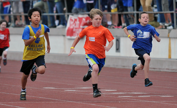 Fifth and sixth grade boys race towards the finish line in the 100-meter sprint.