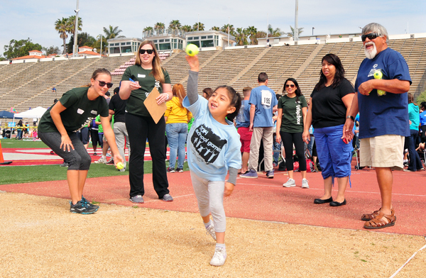 Community volunteers watch an enthusiastic young thrower compete in the ball throw at the School Games at Santa Barbara City College.