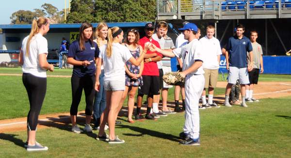 Dos Pueblos softball player Maddie Buie is handed a ball from a Foresters player to throw out the ceremonial first pitch at last year's Presidio Game Day.