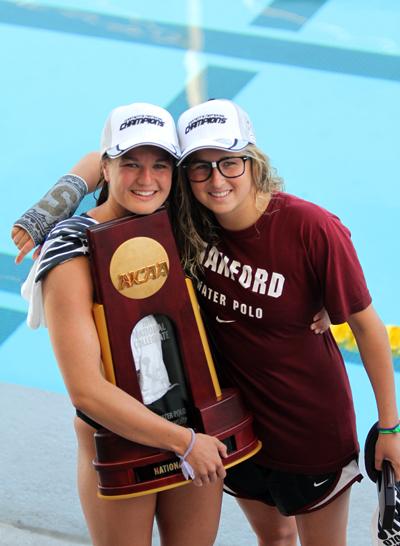 Sisters Kiley Neushul, left, and Jamie Neushul pose with the NCAA Championship trophy.