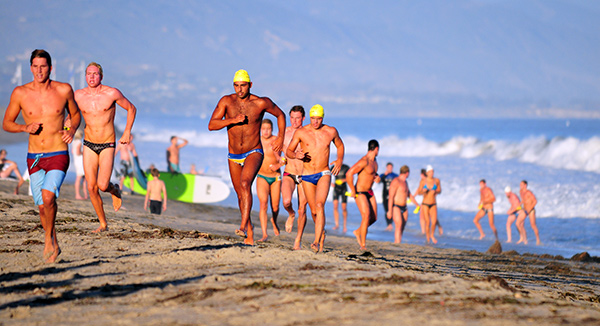 UCSB water polo players race up the beach to the finish line of the ocean swim.