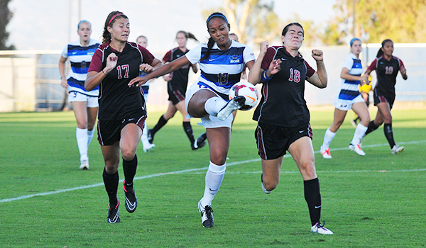 UCSB's Sydney Fuertes keeps the ball away from Westmont's Kelsey Steck, left, and Sophie Fuller, right.