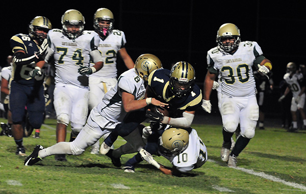 SB's Jeremiah Nicholson (10) and Adam Ebeling (8) stop Dos Pueblos' Angel Davison from reaching the end zone on DP's second-to-last play.