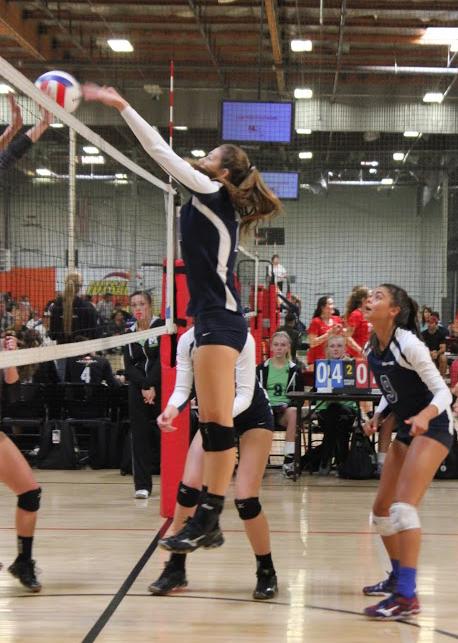 Aubrey Knight of the SBVC 16-Blue blocks a ball as teammate Gabi Peoples looks on.