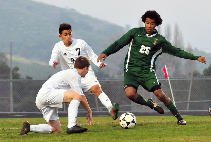 Dos Pueblos defender Jonathan Garcia pokes the ball away from Santa Barbara's Ignacio Rendon.