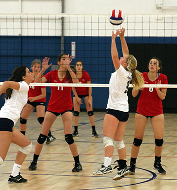 Grace Crozier sets a ball to Marla Ochoa, left, for the 15 White Team. (Courtesy Photo)