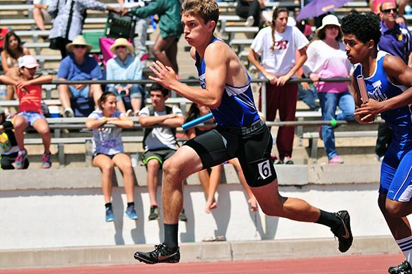Tyson Miller runs a relay leg for the San Marcos varsity boys.