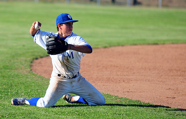 San Marcos' Kyle Gonzalez throws from his knees for an out at third base after a diving stop.