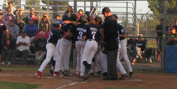 Aiden Johson is mobbed at home plate after his second-inning grand slam in the championship game against Santa Paula.