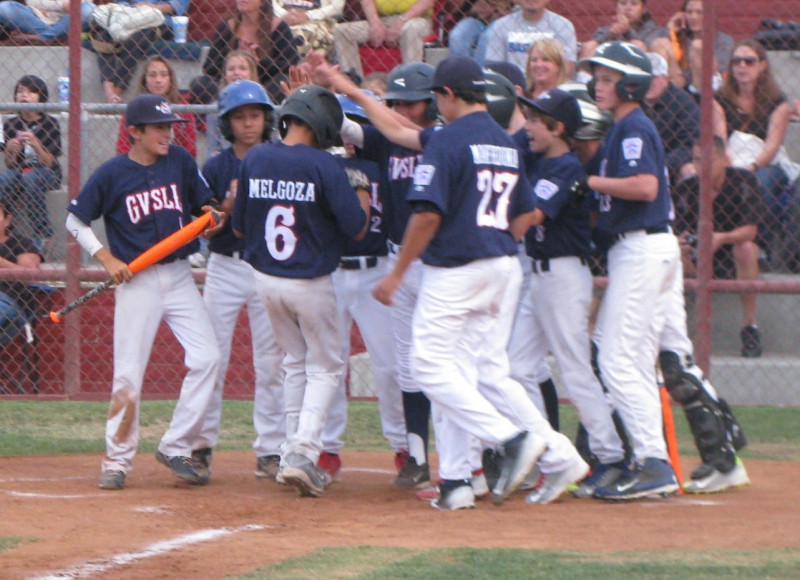 Buddy Melgoza is mobbed by his Goleta Valley South All-Star teammates after belting a grand slam in the first inning of Wednesday's 18-1 win.